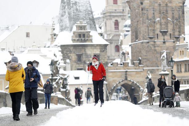 Nainen hiihti keskiaikaisen Kaarlensillan keskelle luotua latua pitkin Tšekin Prahassa.
