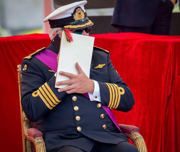 Prinssi Laurent yritti piiloutua ohjelmalehtisen taakse puhelimensa kanssa.