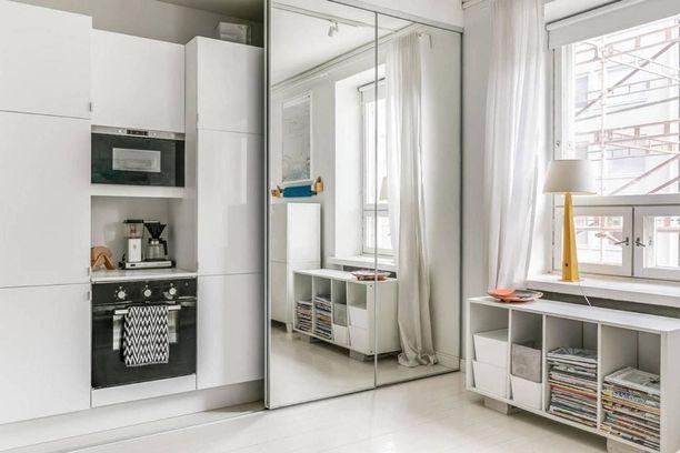 Kaksion valkoinen keittiö jakautuu kahdelle seinälle. Toisen osan eteen on laitettu liukuovet, joten keittiö voi olla esillä tai piilossa tilanteen mukaan. Melko nerokasta, eikö?