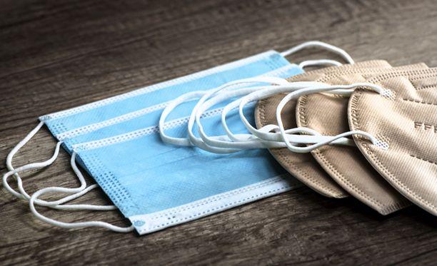 Asiantuntijan mukaan kirurginmaskeissa (sininen) ongelmana on erityisesti niiden huolimaton käyttö. FFP2-maski (kuvassa ruskea) istuu kasvoille napakammin.