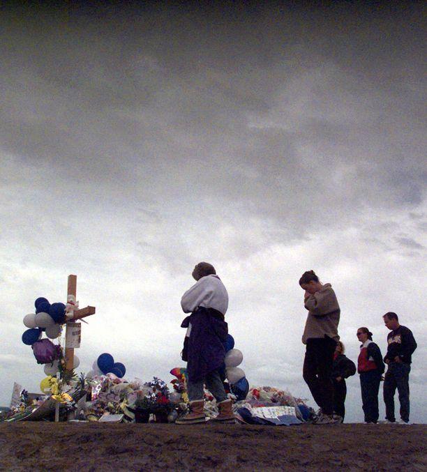 Ihmiset surivat uhreille pystytetyllä muistomerkillä viikko tapahtuneen jälkeen huhtikuussa 1999.