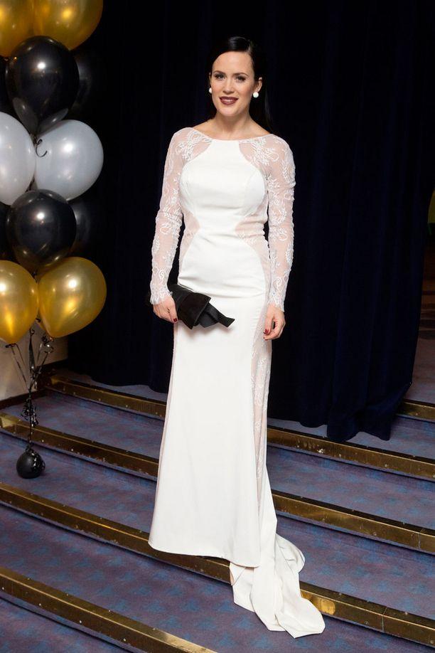 Martina edusti gaalassa valkoisessa pitkähihaisessa mekossa.