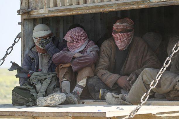 Ihmisiä kuorma-autosaattueessa, joka evakuoi siviilejä ja Isis-terroristien perheenjäseniä Baghusista, Isisin viimeisestä saarekkeesta. Kuva on otettu keskiviikkona.