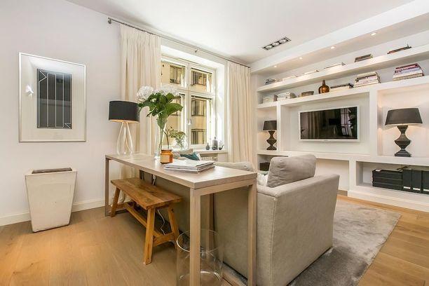 Kaikki seinällä. Kiinteät liki kattoon saakka ulottuvat hyllyt sopivat hyvin pieneen tilaan. Pöytä sijoitettuna aivan sohvan selkämykseen säästää myös tilaa eikä jätä sohvaa keskellä huonetta irtonaisen näköiseksi.