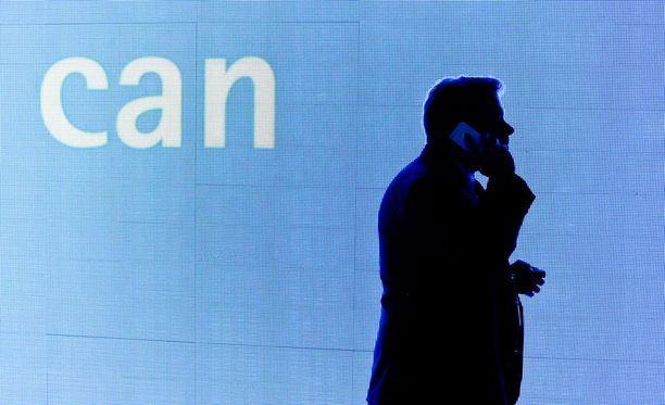 Mies puhelimessa vuoden 2014 Mobile World Congress -messuilla. Tämän vuoden MWC:ltä odotetaan uutisia 5G:n edistymisestä.