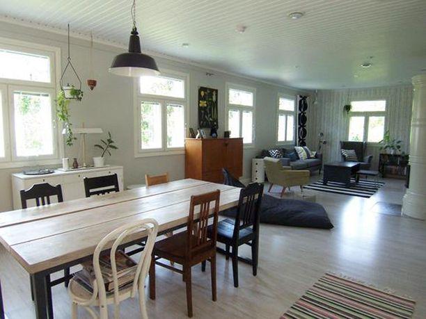 Ruokailutila ja olohuone yhdistyvät yhdeksi suureksi tilaksi.