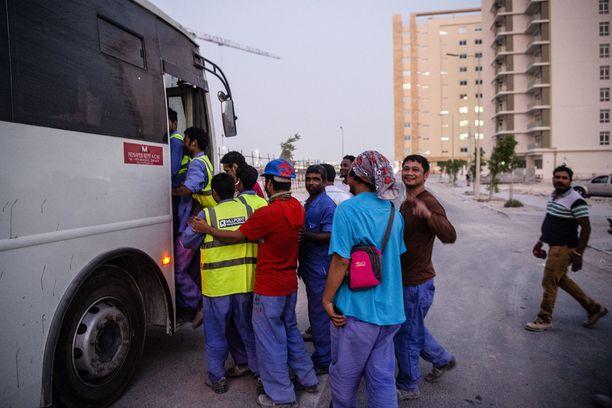 Jalkapallon MM-kisojen stadioneita rakentava työporukka kulkee työpäivän jälkeen bussilla takaisin omalle asuinalueelleen. IL vieraili työmailla lokakuussa.