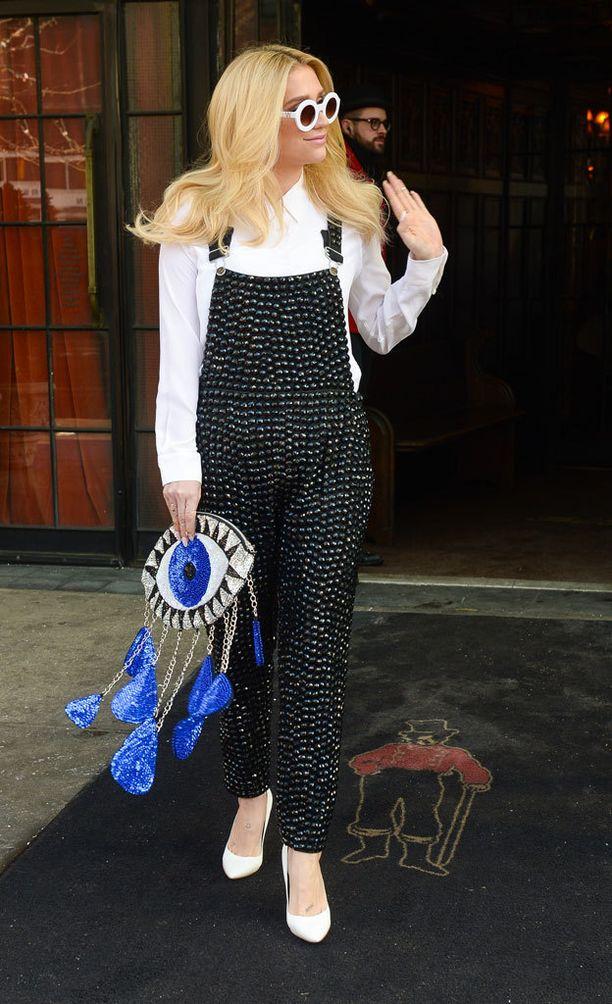 """Kesha ja """"nextin levelin"""" niittihaalarit. Muut laulajan valkoiset vaatteet matchasivat hienosti toisiinsa, ja asun katseenvangitsijana toimi hauska laukku. Loistava asu juhliin."""