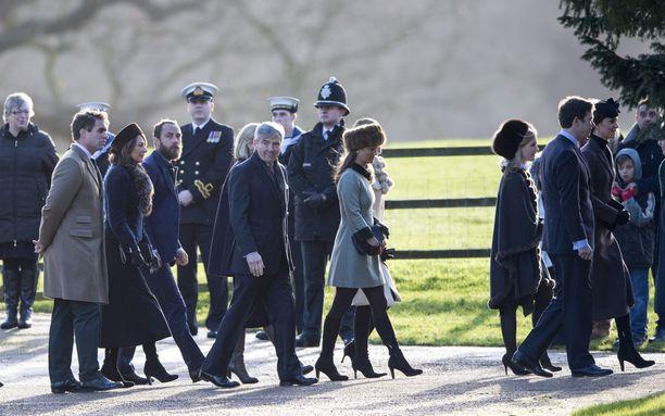 Pippa käveli siskonsa vanavedessä. Partasuinen James tallusteli Carole-äidin rinnalla, ja harmaapäinen Michael-isä kaksikon edellä.