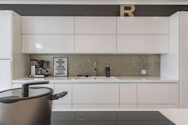 Valkoinen keittiö saa hauskaa rosoisuutta välitilasta, johon on valittu persoonallinen väri. Simppeliin keittiöön maastoutuvat täydellisesti niin jääkaapit kuin muut kaapistot.