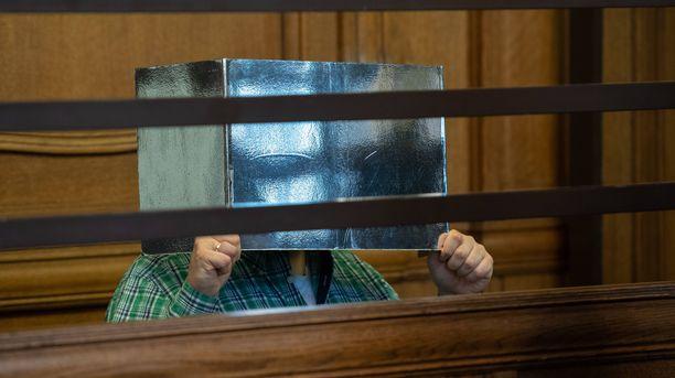 Syytetty peitti kasvonsa oikeudessa. Syyttäjän mukaan murhalla oli seksuaalinen motiivi.
