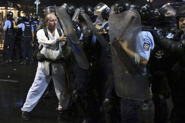 Romanialainen protestoija ja mellakkapoliisi Bukarestin mielenosoituksissa.
