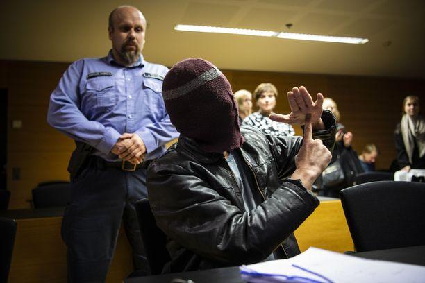 Enona tunnettu mies peitti kasvonsa käräjäoikeudessa sekä esitteli hämmentäviä käsimerkkejä.