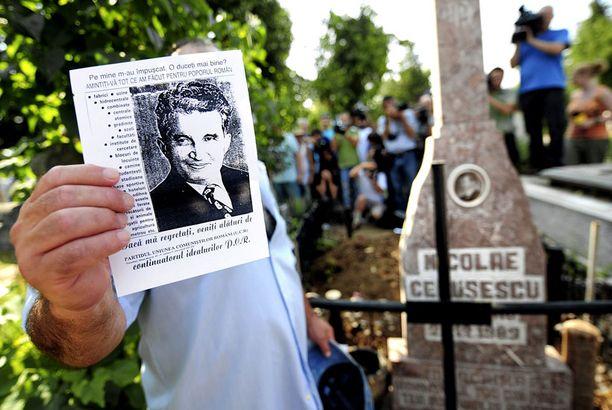 Mies piteli Nicolae Ceausescun kuvaa diktaattorin haudalla Bukarestissa.