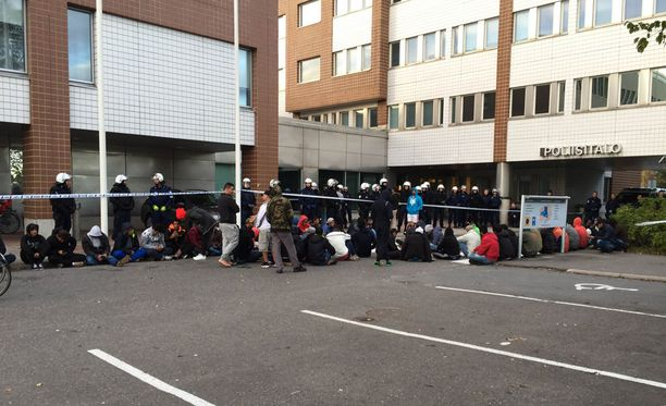 Turvapaikanhakijat osoittavat mieltään Oulun poliisiaseman edessä.