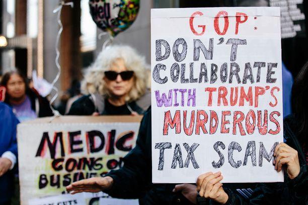 """Mielenosoittaja vaati Trumpin tornin edustalla New Yorkissa viime viikolla, ettei republikaanipuolue tukisi Trumpin """"murhanhimoista verovedätystä""""."""