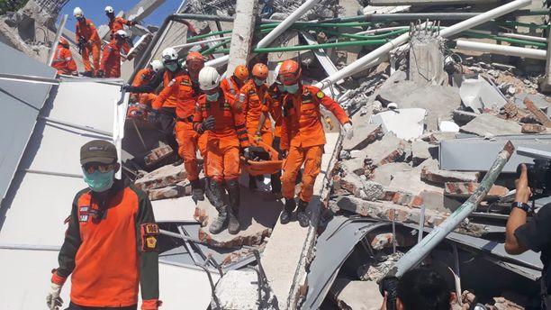 Pelastajat kantoivat kuolleita ulos sortuneesta rakennuksesta Palussa sunnuntaina.
