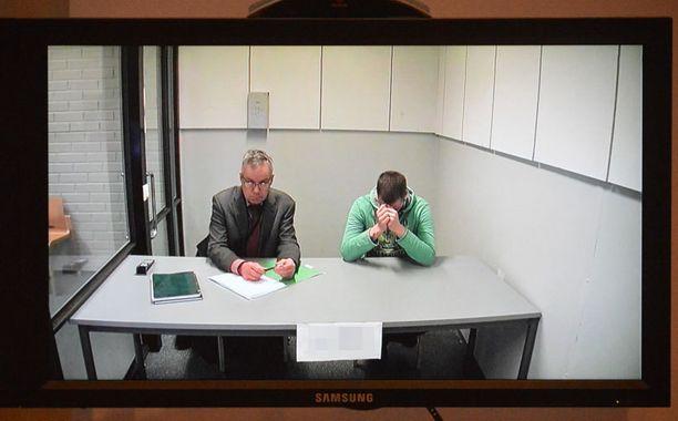 Kotkalaisen asianajajan murhan tunnustanut epäilty (oik.) istui valmistelevan istunnon aikana Vantaan vankilan videohuoneessa yhdessä asianajajansa Timo Kallion kanssa.