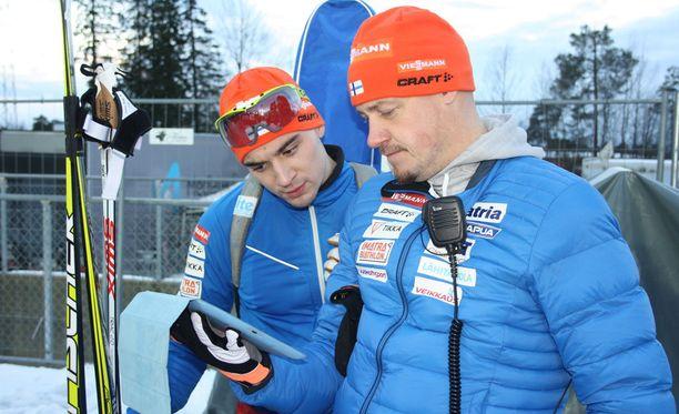 Olli Hiidensalo (vas.) ja Suomen päävalmentaja Marko Laaksonen tutkivat kilpailuanalyysiä miesten 10 kilometrin mittelön jälkeen.