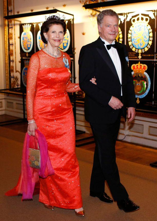 Kuningatar Silvia valitsi illallisille upean punaisen iltapuvun, jota koristavat strassit ja pieni laahus.