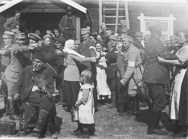 Itsenäisyysvuosi 1917 vaihtui pian veriseen sisällissotaan. Kuvassa valkoiset mäntyharjulaiset juhlivat Mäntyharjun aseman Penttilän talon pihalla kansalaissodan lopulla. 17.4.1918