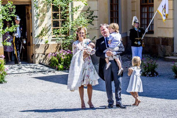 Prinsessa Madeleine sylissään prinsessa Adrienne. Vierellä Chris O'Neill sylissään prinssi Nicolas. Isänsä oikealla puolella on prinsessa Leonore.