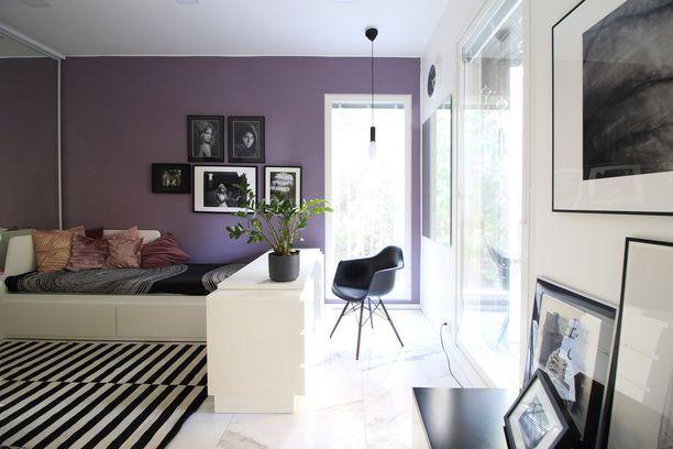 Värikästä seinää ei kannata pelätä. Tässä kuvassa violetti tekee tehtävänsä ja tuo huoneeseen eloa ja persoonaa. Muuramen kalusteet ovat edustamassa suomalaista designia.