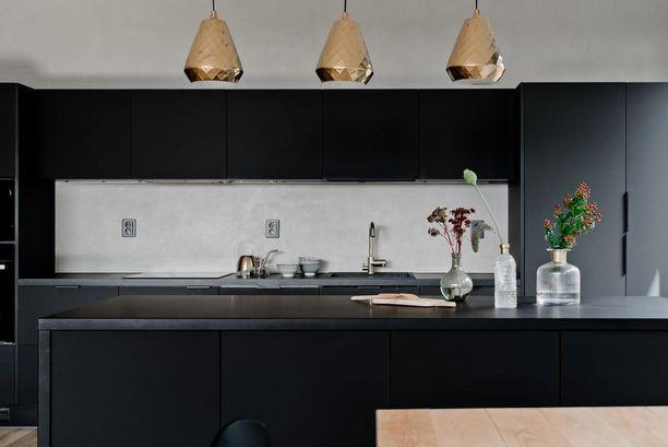 Metallinhohtoiset lampunvarjostimet ja maljakot sopivat mainiosti mustan pariksi. Sysimusta keittiö on dramaattinen, mutta vaalea välitila saa sen hengittämään.