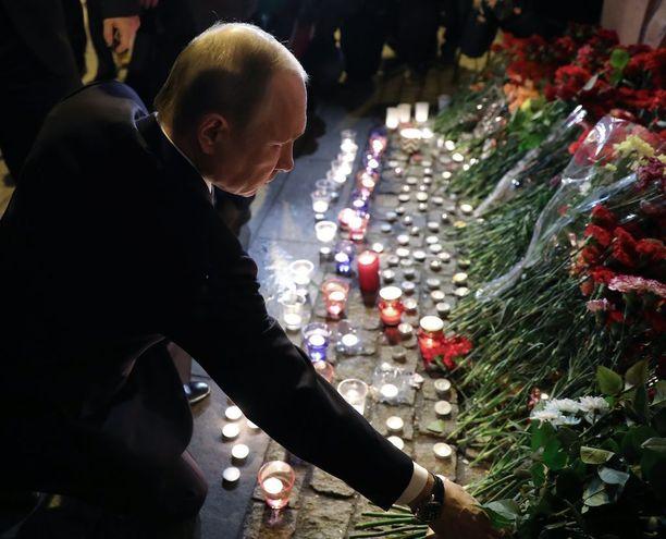 Presidentti laski kimpun punaisia ruusuja uhrien muistoksi.
