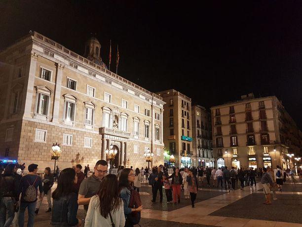 Paikalliset ihmiset jännittävät, saapuuko Katalonian syrjäytetty aluejohtaja Carles Puigdemont Placa de Sant Jaunella sijaitsevalle hallintorakennukselle.