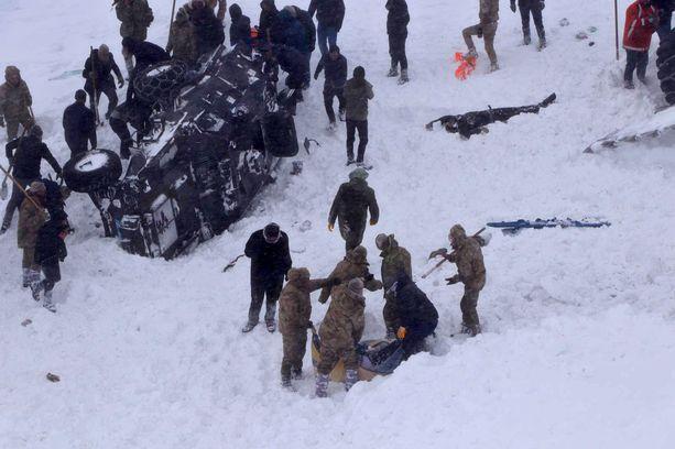 Sotilaat ja pelastusmiehet etsivät lumivyöryn alle hautautuneita.