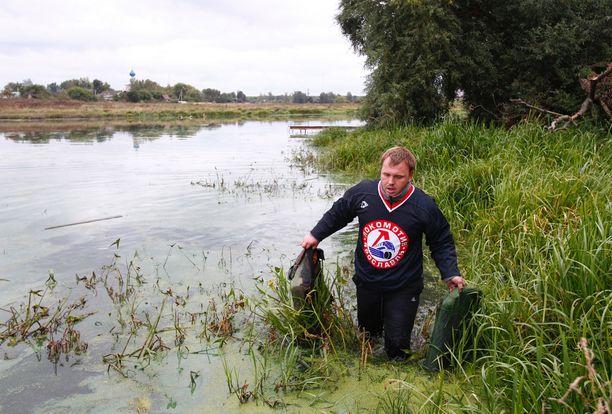 Lokomotiv Jaroslavl -paitainen mies nosti onnettomuuskoneen tavaroita joesta.