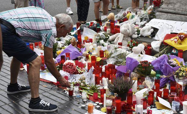 Ihmiset jättivät kukkia iskupaikalle La Rambla-kadulla.