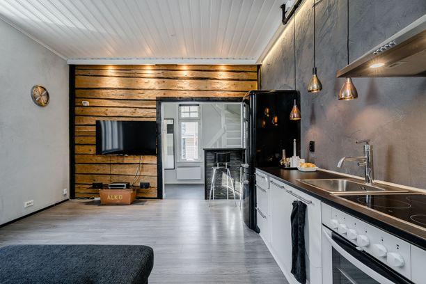 Olohuoneessa menneisyys ja nykyisyys kohtaavat. Moderni keittiö ja vanha hirsiseinä tuovat yhdessä kontrastia.