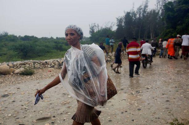 Nainen varusti itsensä sadetakilla Haitin Tabarressa.