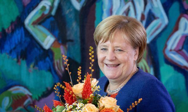 Liittokansleri Angela Merkel piti käsissään liikenneministerin syntymäpäiväkukkia.