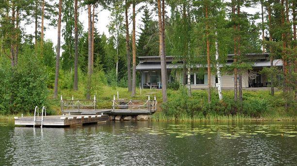 Tukevarakenteinen laituri kestää isommankin veneen kiinnityksen. Hirsihuvilan ikkunat avautuvat järvelle.