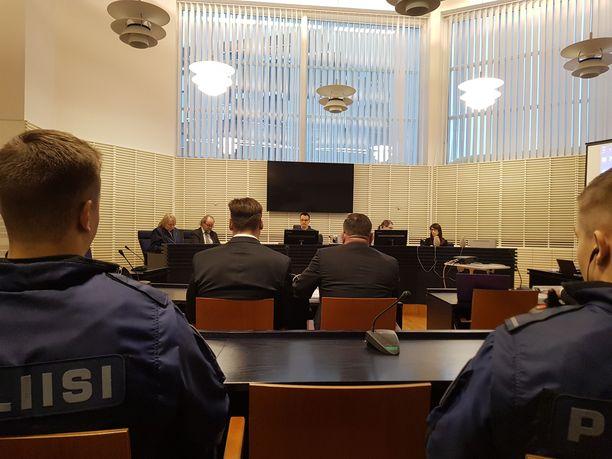 Poliisimiesten ja harjoittelussa olevien poliisiopiskelijoiden rivi erotti Huohvanaisen (edessä vas.) yleisöstä.