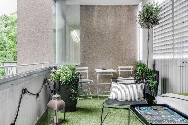 Vihreä matto ja viherkasvit tuovat parvekkeelle puutarhamaisen tunnelman. Illalla parvekkeen valaisee hauska valoketju.