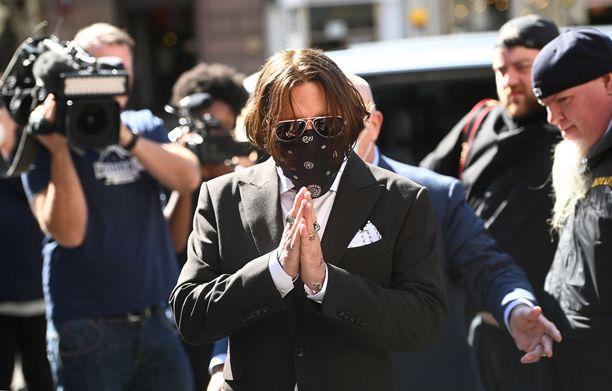 Johnny Depp saapui oikeuteen pukuun, aurinkolaseihin ja kasvohuiviin sonustautuneena.