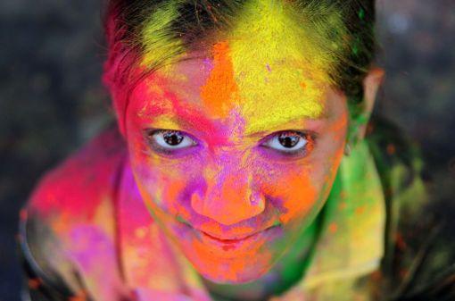 Intialaistyttö poseerasi värien peitossa.