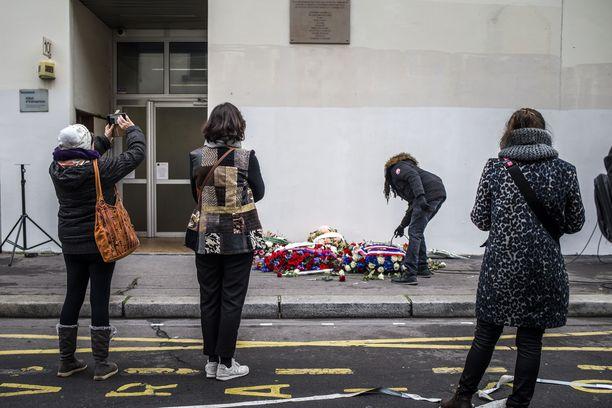 Ihmiset laskivat kukkia Charlie Hebdon entisen toimituksen eteen hyökkäyksen vuosipäivänä 7. tammikuuta 2020.