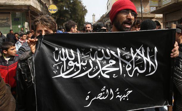 Mielenosoittaja heilutti al Nusra -järjestön lippua Syyriassa vuonna 2013. Al Nusra on yksi al-Qaidan alaisista järjestöistä.