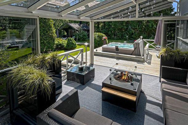 Lasitetulle terassille tunnelmaa tuovat viherkasvit ja sohvat. Huomaa erikoinen tulipöytä.