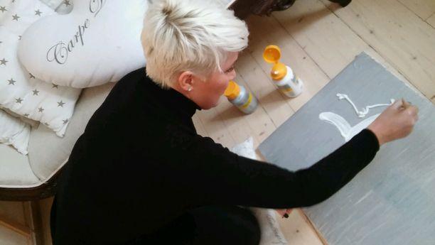 Mira Kasslin maalaa huutokauppaan omaa teostaan.