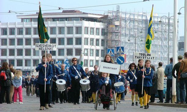 Töölöläiset Ilvesveikot ja Töölön Tähystäjät lippukunnat marssivat rumpupatteriston tahdissa.