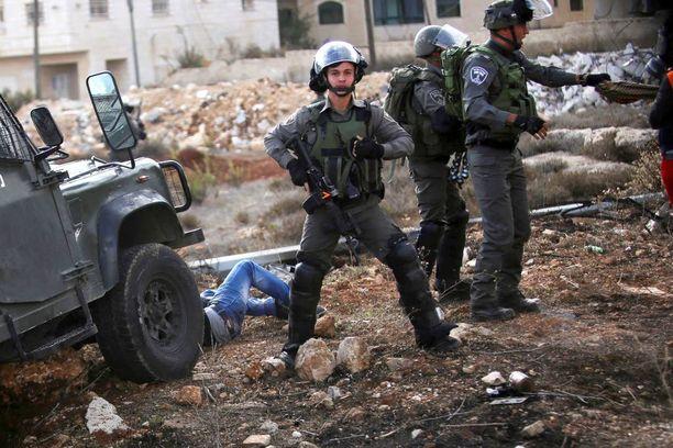 Israelin poliisi seisoi vahdissa perjantaina sen jälkeen, kun heidän jeeppinsä oli osunut palestiinalaiseen mielenosoittajaan Länsirannalla.