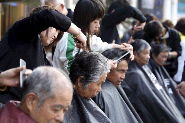Vapaaehtoistyöntekijät huolehtivat vanhusten hiustenleikkauksesta Shanghaissa.