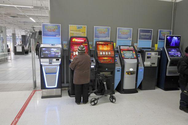 Seniori pelaa rahapeliä Sokoksella Joensuussa. Lidlin päätös poistaa automaatit panee kaupan jättiläiset S-ryhmän ja Keskon selkä seinää vasten.