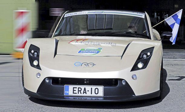 """E-RA kiihdytti Suomen lippu hulmuten kohti sähköautojen taistelukenttää Berliinissä. Design Contest -palkinto on konepellin päällä, Battery Electric rallin """"poikakin"""" oli tulossa ja extrana kunniapalkinto."""